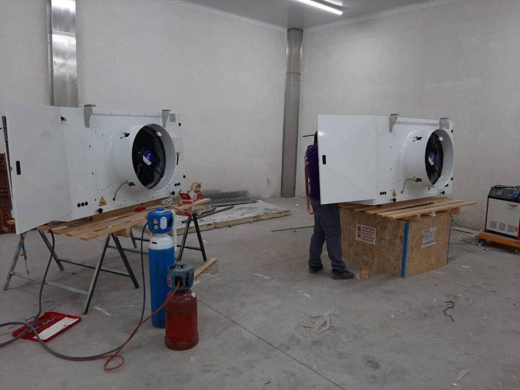 Dos trabajadores instalan evaporadores Zanotti para el conducto textil del obrador